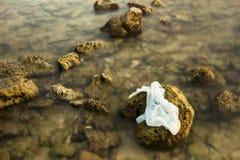 Sacchetto di plastica bianco sulla spiaggia di pietra nel tramonto thailand immagini stock libere da diritti