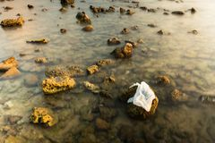 Sacchetto di plastica bianco sulla spiaggia di pietra nel tramonto thailand fotografia stock