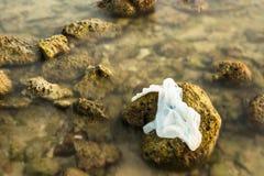 Sacchetto di plastica bianco sulla spiaggia di pietra nel tramonto thailand fotografia stock libera da diritti