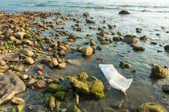 Sacchetto di plastica bianco sulla spiaggia di pietra nel tramonto thailand immagine stock libera da diritti