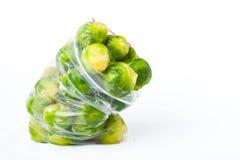 Sacchetto di plastica con i cavoletti di Bruxelles congelati isolati su bianco veget Fotografia Stock Libera da Diritti