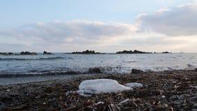 Sacchetto di plastica sulla spiaggia sabbiosa con le onde che colpiscono la riva di mare Inquinamento della spiaggia archivi video