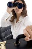 Sacchetto femminile della holding ed osservare con binoculare Immagini Stock