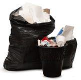 Sacchetto pieno di plastica e del cestino per la carta straccia Immagini Stock