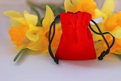Sacchetto rosso del velluto con i fiori gialli su un fondo bianco isolato immagini stock