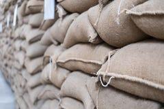 sacchi della canapa che contengono il chicco di caffè nel magazzino sacchi impilati dentro fotografia stock libera da diritti
