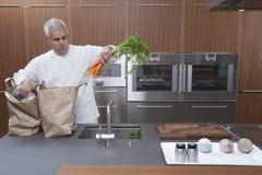 Sacchi di carta di Unpacking Carrots From del cuoco unico in cucina Fotografie Stock