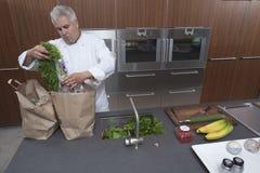 Sacchi di carta di Unpacking Groceries From del cuoco unico in cucina immagine stock libera da diritti
