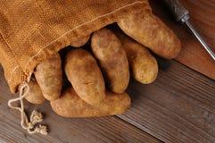 Sacco della tela da imballaggio delle patate su legno Fotografia Stock