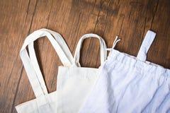 Sacco di acquisto del panno della borsa di eco del tessuto della tela del totalizzatore su fondo di legno - zero sprechi usano di immagini stock