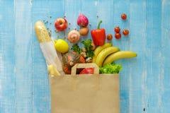 Sacco di carta di alimento salutare differente su fondo di legno blu fotografia stock