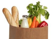 Sacco di carta con alimento sopra bianco Fotografia Stock