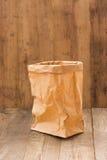 Sacco di carta di Brown su fondo di legno Fotografie Stock Libere da Diritti