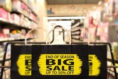 Sacco di carta nero con la conclusione della stagione, grande vendita, fino a 50 per cento o Fotografie Stock
