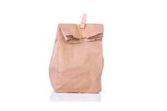Sacco di carta, scatola di pranzo con la molletta per il bucato di legno su fondo bianco Fotografia Stock Libera da Diritti