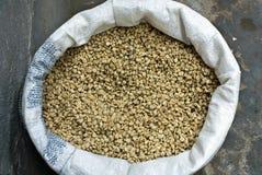 Sacco di iuta con i chicchi di caffè verdi immagine stock
