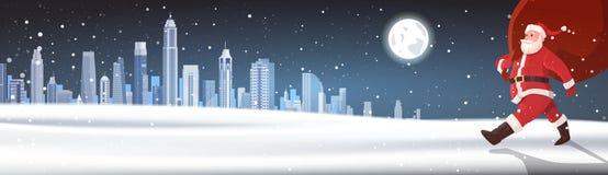 Sacco di Santa Walking With Big Red con i regali sopra l'insegna di orizzontale del paesaggio di Snowy del fondo della città di i Immagini Stock