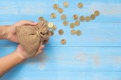 Sacco o sacchetto dei soldi della tenuta con le monete su fondo di legno blu fotografia stock