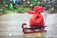 Sacco rosso di Natale con i regali sulla slitta su un fondo di legno con i rami e le ghirlande attillati Fotografia Stock Libera da Diritti