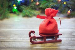 Sacco rosso di Natale con i regali sulla slitta su un fondo di legno con i rami e le ghirlande attillati Fotografia Stock