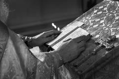 Sacerdote in bianco e nero che prega nella chiesa che tiene la bibbia e l'incrocio dell'agrifoglio con le candele fotografia stock