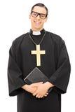 Sacerdote católico joven que sostiene la Sagrada Biblia Imagen de archivo libre de regalías