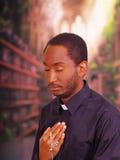 Sacerdote católico que lleva la camisa tradicional del cuello administrativo que se coloca de ejecución de la muestra de la cruz  Foto de archivo libre de regalías