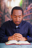 Sacerdote católico que lleva la camisa tradicional del cuello administrativo que se sienta con las manos dobladas que sostienen e Fotografía de archivo