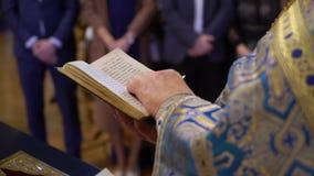 Sacerdote che prega con il libro della bibbia in chiesa archivi video