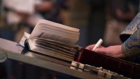 Sacerdote che prega con il libro della bibbia in chiesa stock footage