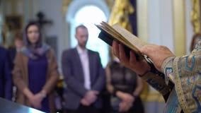 Sacerdote che prega con il libro della bibbia in chiesa video d archivio
