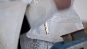 Sacerdote che prega con l'incrocio sul petto in chiesa stock footage