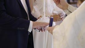 Sacerdote che pregano nella chiesa alla cerimonia di nozze ed anelli sopra messi per le persone appena sposate stock footage