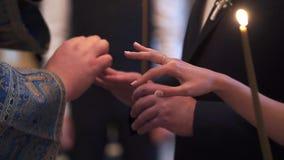 Sacerdote che pregano nella chiesa alla cerimonia di nozze ed anelli sopra messi per le persone appena sposate archivi video