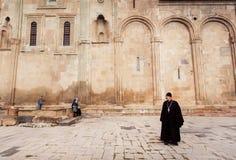 Sacerdote cristiano que se coloca cerca de la pared de piedra ornamental de la catedral de Svetitskhoveli, construida en 4ta Imagenes de archivo