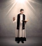 Sacerdote joven en el donante de su bendición Imagenes de archivo