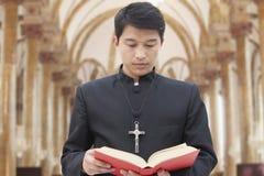 Sacerdote Looking Down en la biblia en una iglesia Imágenes de archivo libres de regalías