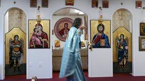 Sacerdote que ruega en el altar de la iglesia ortodoxa rumana metrajes