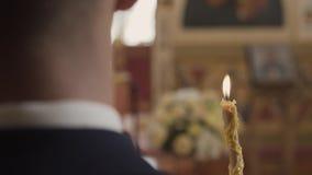 Sacerdote que ruega en iglesia en la ceremonia de boda y puestos anillos para los recienes casados novia y novio metrajes