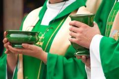 Sacerdotes cristianos que sostienen los tazones de fuente de oblea y de vino imagen de archivo libre de regalías