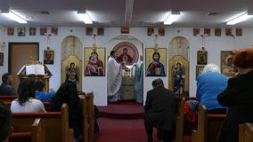 Sacerdotes que ruegan en el altar de la iglesia ortodoxa rumana almacen de video