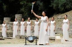 A sacerdotisa alta, a chama olímpica durante a iluminação da tocha cere Imagem de Stock Royalty Free