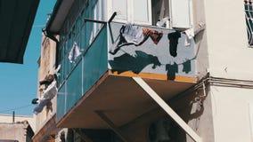 Sachen, zum auf Seilen unter der Stadtsonne zu trocknen Die Abnutzung der gewaschenen Männer trocken auf Seil am Balkon Sachenfal stock video footage