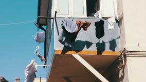 Sachen, zum auf Seilen unter der Stadtsonne zu trocknen Die Abnutzung der gewaschenen Männer trocken auf Seil am Balkon Sachenfal stock footage