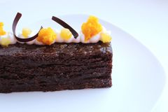 Sacher与杏子片的奶油蛋糕蛋糕和在白色板材的橙色微波海绵装饰 免版税库存图片