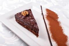 sacher巧克力蛋糕片断,与核桃装填的可可粉饼干和黑暗的巧克力结冰在板材服务 图库摄影