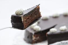 Sacher-Torte auf Metalllöffel, Geburtstagskuchen auf weißer Platte, Konditorei, Schlagsahne auf Kuchen, Fotografie für Shop, Scho Stockfotografie