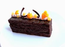 Sacher Torte cake with apricot pieces and orange microwave sponge decoration on white royalty free stock image