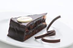 Sacher torte, chocolade scherp met wervelingen op witte plaat, zoet dessert, patisserie, fotografie voor winkel stock foto