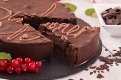 Sachertorte. Sacher torte with red currant on black dish Stock Photo